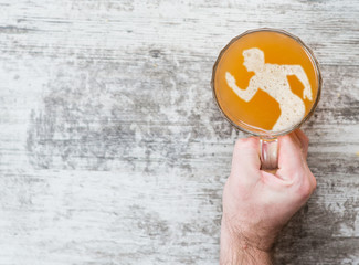 Fotobehang Bier / Cider man's hand holds a mug of beer with a silhouette of a running man. Top view. Space for text