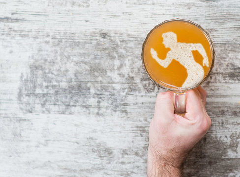 man's hand holds a mug of beer with a silhouette of a running man. Top view. Space for text