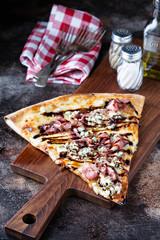 Big slice of pizza with prosciutto, blue cheese