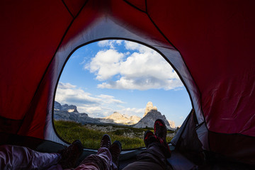 Tuinposter Kamperen Bivouac at Tre Cime di Lavaredo, family resting in tent, red illuminated tent on pass in Dolomites, Italy