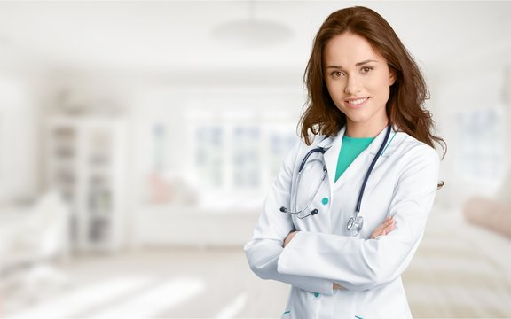 Young female doctor with stethoscope on blurred hospital