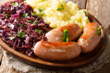 Home-style meal of mashed potatoes with fried red cabbage and sausages close-up on a plate. horizontal