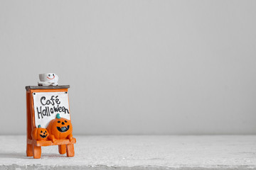 Halloween festival Head Doll Pumpkins  haunted spooky with coffee cup on top and text cafe halloween decoration on wood background. Blank space available for your text.
