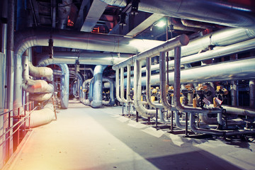 Equipment, cables and piping as found inside of a modern industrial power plant. Industrial zone, Steel pipelines, valves, cables and walkways