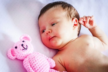 Cute newborn baby girl lying in the cradle and looking at a pink teddy bear. Several weeks old infant stock image.