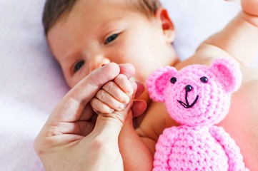 Father holding a tiny hand with fingers of a sweet adorable newborn baby girl with a pink teddy bear in the frame.