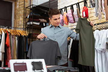 Grey or green. Attractive young man doing shopping and thoughtfully looking at the T shirts in his hands
