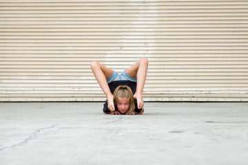 Flexible Girl On Her Chest With Her Back Arched and Her Feet Hanging Down By Her Face