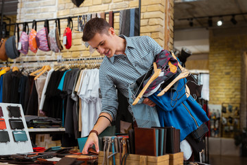 Discount. Positive young man doing shopping and looking at nice wallets while holding big amount of clothes