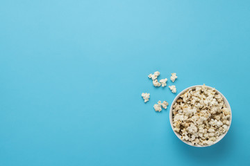 Bowl with popcorn on a blue background. Concept home theater, mo