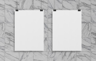 Two blank white poster hanging up with clips mockup