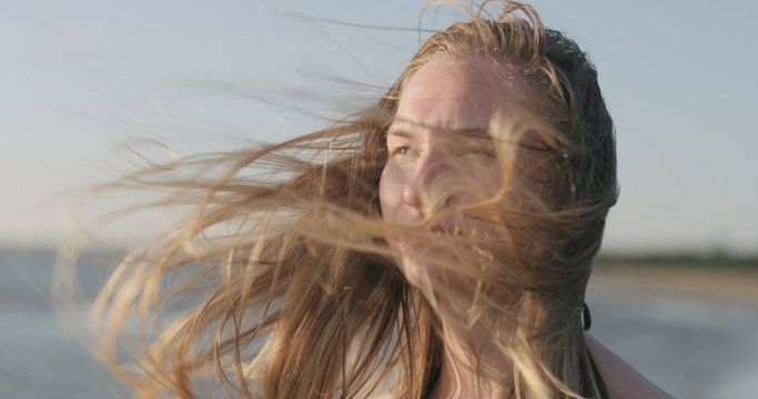 closeup portrait of young girl standing on a beach and wind blows her hair