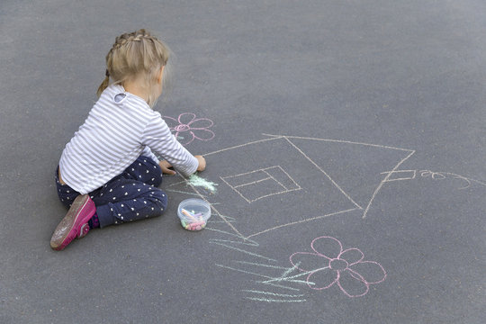 Little preschool caucasian girl drawing a house with chalks on the pavement