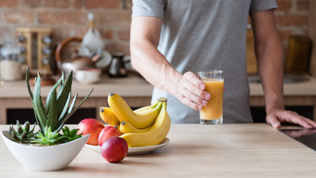 healthy eating habit. unrecognizable man holding a glass of freshly squeezed fruit juice. natural organic banana and nectarine drink. balanced diet and nutrition.