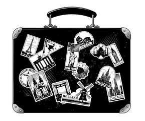 Old black luggage with landmarks travel labels isolated on white