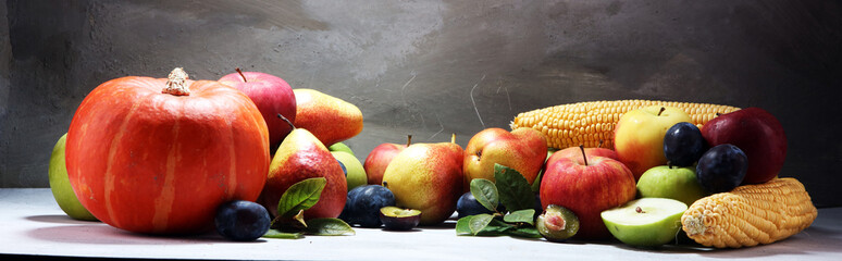 Various fresh fruits. Thanksgiving pumpkin, apples, and maize on rustic background.