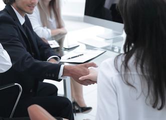 closeup.handshake trading partners,sitting behind a Desk