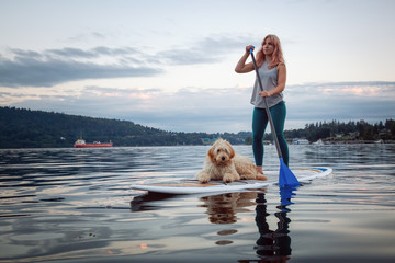 Girl with a dog on a paddle board during a vibrant summer sunset. Taken in Deep Cove, North Vancouver, BC, Canada.