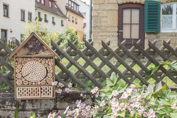 Bienenhotel vor Bauernhaus mit Jägerzaun und Herbstanemonen
