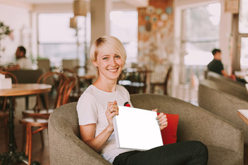 Young happy woman sitting in restaurant and holding photo album