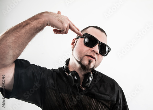 portrait of a badass rapper in sunglasses with headphones on a w