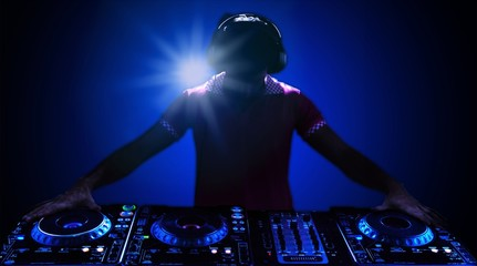 Portrait of confident young DJ with headphones on head mixing