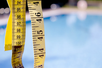 Measuring tape on pool background