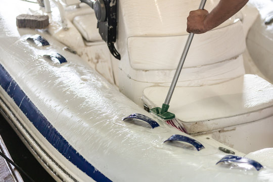 Man washing white inflatable boat with brush and pressure water system at garage. Ship service and seasonal maintenance concept