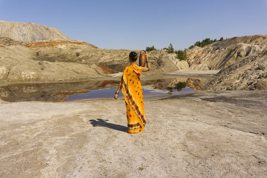 a girl in a sari with a pitcher on her shoulder goes for water to a dirty lake in a deserted landscape