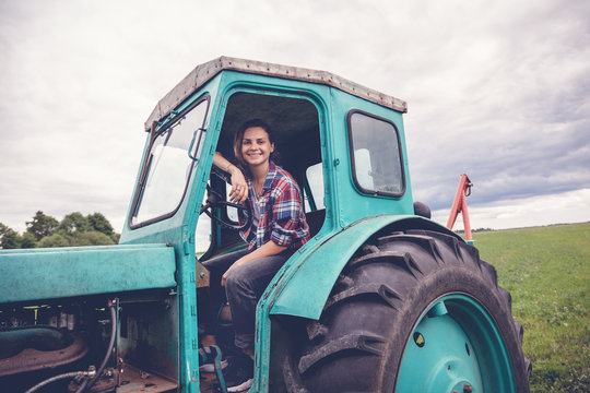 Young beautiful girl working on a tractor in the field, unusual work for women, gender equality concept