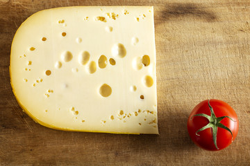 One piece of Emmentaler swiss chese and one little cherry tomato