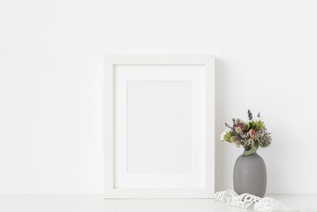 White a5 portrait frame mockup with dried field wild flowers in vase and vintage lace on white wall background. Empty frame, poster mock up for presentation design.