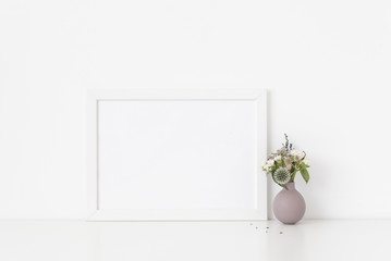 White a4 landscape portrait frame mockup with bouquet of dried flowers in cute small vase on white wall background. Empty frame, poster mock up for presentation design.