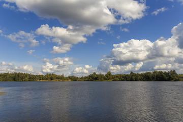 группа больших белых кучевых облака, плывущих над лесным озером в качестве природного фона