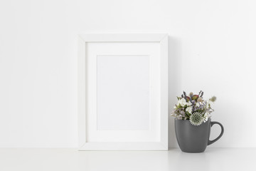 White A5 portrait frame mockup with dried field wild flowers in gray mug on white wall background. Empty frame, poster mock up for presentation design. Template frame for text, lettering, modern art.