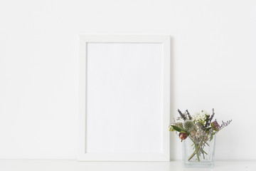 White a4 portrait frame mockup with dried field wild flowers in transparent vase on white wall background. Empty frame, poster mock up for presentation design.