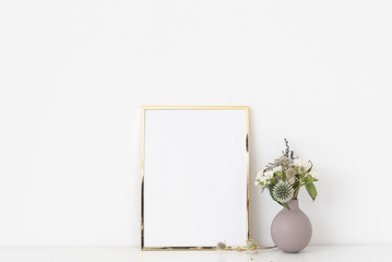 Cute gold a5 portrait frame mockup with dried field wild flowers in small vase on white wall background. Empty frame, poster mock up for presentation design.