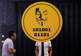 Men chat next to a sign for an exhibition during Internet Security Conference 2018 in Beijing