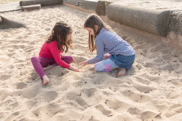 Little girls with bare feet sitting and playing together in sand pit at fenced playground with afternoon shadows (selective focus)