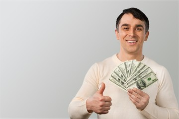 Happy Man Holding Money and Giving Thumb Up - Isolated