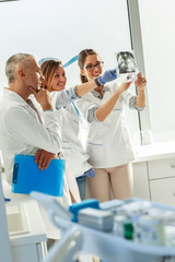 Group of dentists examining x-ray image of patients teeth. Standing in new bright dentist office.