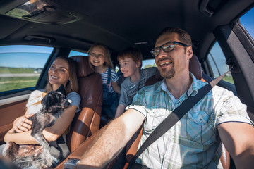 cheerful family with two children goes to the car
