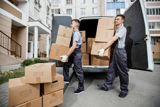 Two young handsome smiling workers wearing uniforms are unloading the van full of boxes. The block of flats is in the background. House move, mover service.