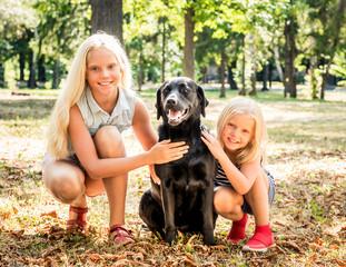 Little blond girls sit hugging a black dog in a park