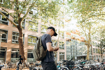 A student with a backpack or a tourist on Leipzig Street in Germany uses a cell phone next to the bicycle parking which is next to the library of the University of Leipig and student hostel.