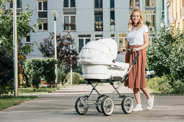 mother walking with baby stroller on street
