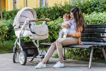 mother sitting with baby on bench near stroller in park