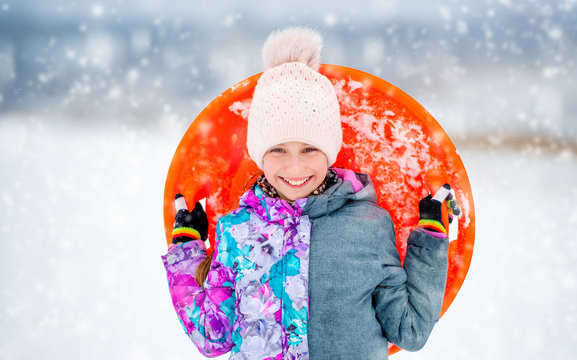 Funny girl with saucer sled outdoors
