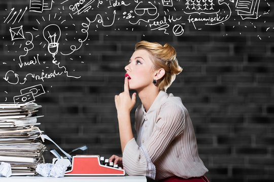 Attractive young woman working on vintage typewriter on