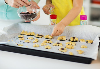 family, cooking and baking concept - mother and little daughter with chocolate sprinkles decorating cookies on tray at home kitchen